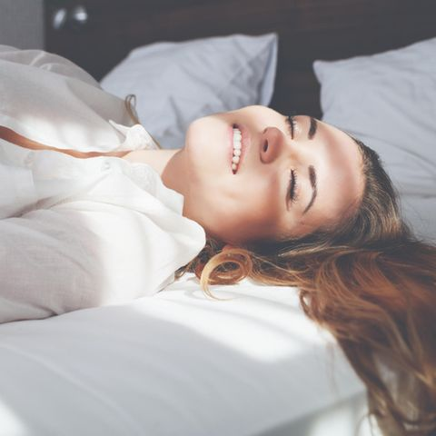 Frau liegt im Bett, weiße Kleidung, lächelt