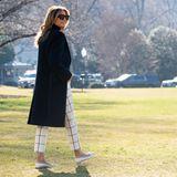 Bei ihrer Abreise trug die First Lady eine karierte weiße Hose und einen dunklen Mantel. Dazu kombiniert sie elegante Ballerina-Pumps und eine große Sonnenbrille.