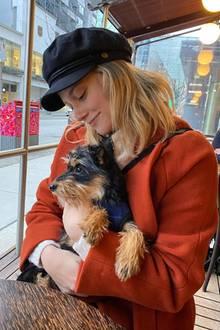 Lili Reinhart sitzt mit ihrem Hund im Café