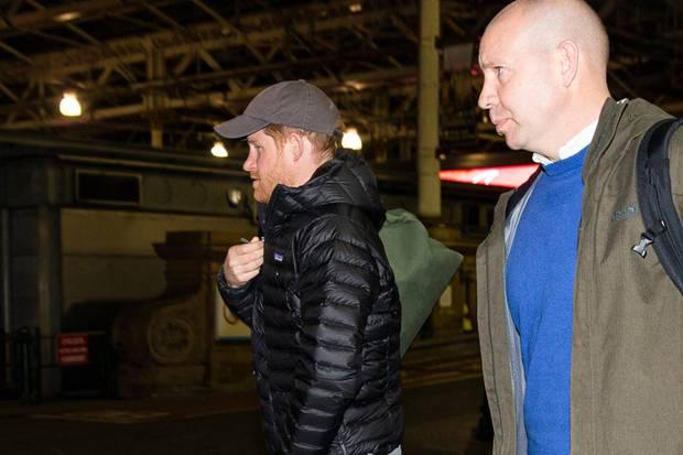 Begleitete von Sicherheitspersonal geht Prinz Harry zum Wagen