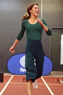 Zu einem dunkelgrünen, hautengen Oberteil mit Rundhalsausschnitt kombiniert die strahlende Kate eine farblich passende Culotte mit Bügelfalte von Zara. Coole Sneaker von Marks & Spencer - ebenfalls mit grünen Streifen - runden den sportlich-eleganten Look ab.