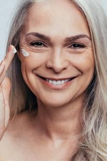 Frau trägt Anti-Aging Creme auf Gesicht auf