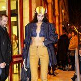 Ein bisschen Reggae-Feeling für zwischendurch gefällig? Gern. Bella Hadid trägt zur senfgelben Jeans ein bauchfreies Denim-Top und eine farbenfrohe Strickmütze.