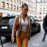 Ihre Kunstlederhose von Leo kombiniert Bella Hadid mit Sonnenbrille, Weste und Jacke von Chanel. Die klobigen weißen Trendsneaker stammen von Li-Ning Atmos.