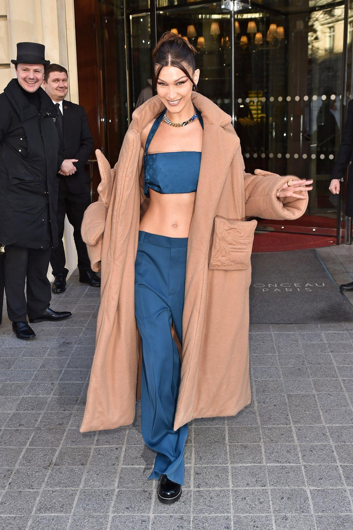 Solche Bauchmuskeln muss man zeigen - selbst im tiefsten Winter. Bella Hadid trägt über ihre Jeans-Kombination bestehend aus Micro-Top und Wide-Leg-Hose einen langen, camelfarbenen Oversize-Mantel.