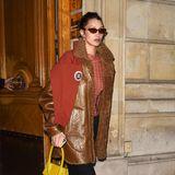 Stilvolle Erdfarben, gepaart mit einer knalligen It-Bag von Jacquemus - so verlässt Bella Hadid einen Fittingtermin für die Paris Fashion Week.