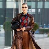 """Ihre Vorliebe für vermeintlich spießigeNerd-Pullover verbindet Bella Hadid bei diesem Look mit einem Lederoutfit in bester """"Wild Wild West""""-Manier."""