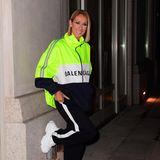 In einem neongelbenZipper des Labels Balenciaga und passender Jogging-Hose mit weißem Streifen an den Seiten, posiert Celine Dion lässig an einer Hausmauer in New York. Weiße Sneaker runden den locker-sportiven Look der Sängerin gekonnt ab.