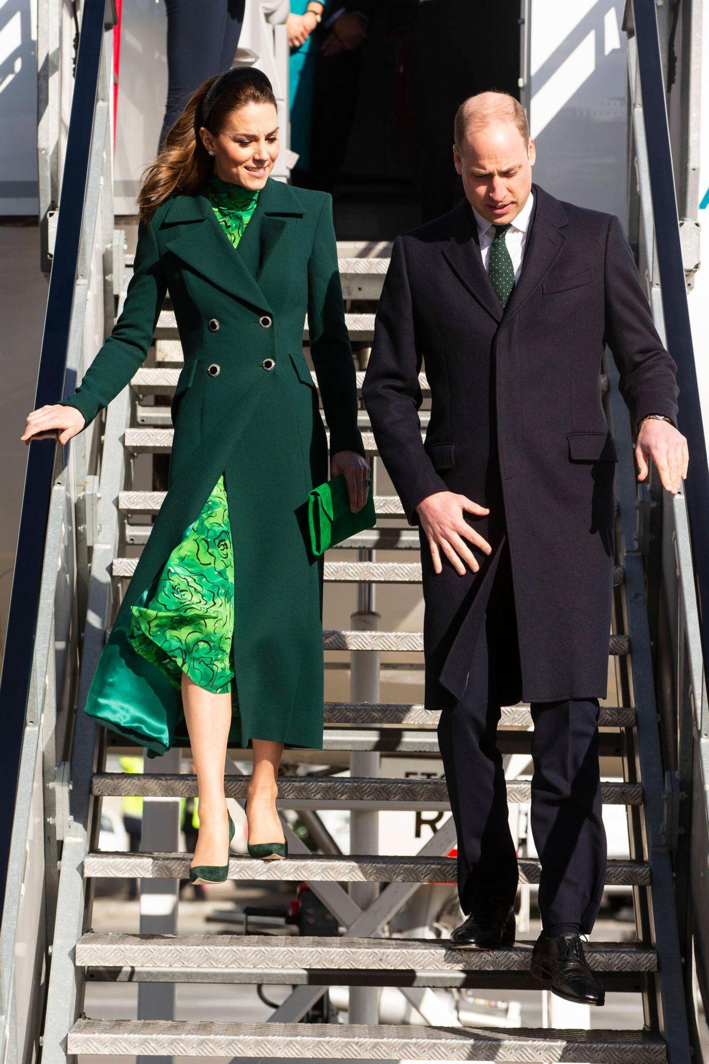 Auch gegen die Brise ist Herzogin Catherine gewappnet: Ein schwarzer Samt-Haarreif von Jane Taylor hält ihr das wehende Haar aus dem Gesicht. Ihre Accessoires,Pumps von Emmy London und eine Clutch von LK Bennett, machen den grünen Look perfekt.