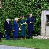 """Die Gruppe verschlägt es in den Garten.Dort läuten Herzogin Catherine und Prinz William die Friedensglocke. Aufmerksame Beobachter werden erkennen, dasssich jemand dazu geschlichen hat: Brod, der Hund des Präsidenten, schaut genau hin, was in seinem Revier vor sich geht. Offenbar ist er einverstanden: kein einziges Bellen ist zu hören. Die mitgereiste Presse ist begeistert. Ihr Urteil: """"Brod ist ein braver Hund""""."""