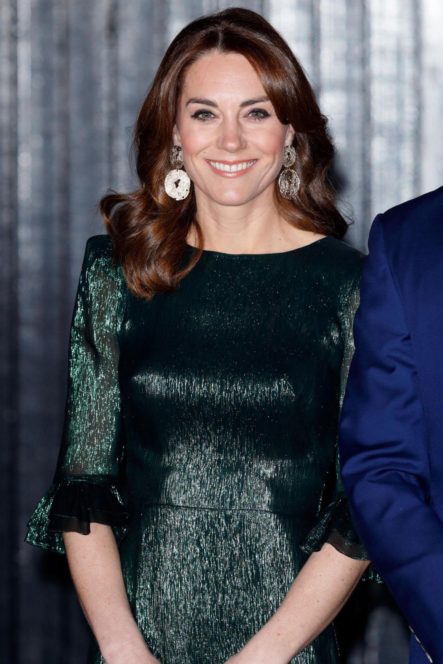 """Beim Empfang des britischen Botschafters in Irland wählt Herzogin Kate erneut einen stylischen Look in der Nationalfarbe des Landes. Die dunkelgrünen Metallic-Fäden des Midi-Kleides lassen Katestrahlen, die Volant-Borde an Saum und Ärmel verleiht dem """"The Vampire's Wife""""-Kleid das gewisse Extra. Kostenpunkt des Kleides: 1.900 Euro."""