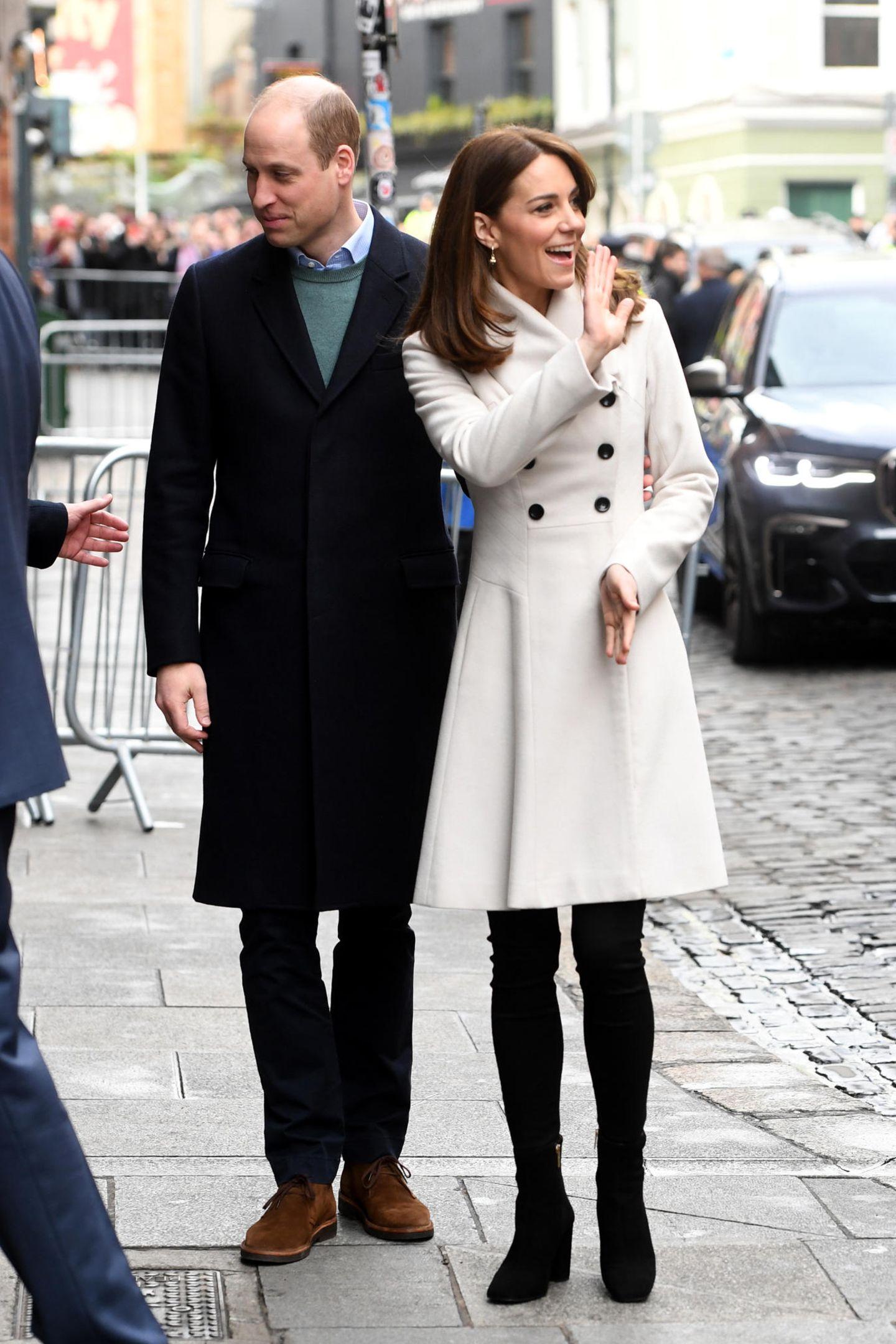 Ihr Look ist eine absolute Punktlandung! Sie trägt einen cremefarbenen Mantel von Reiss, in dem wir sie schon vor ihrer Hochzeit mit Prinz William gesehen haben. Er hängt also seit mindestens 10 Jahren im Kleiderschrank der Dreifach-Mama. Dazu kombiniert sie eine schwarze Jeans von Zara.