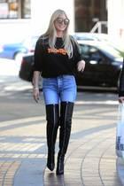 """Heidi Klum beweist, dass man selbst mit 46 Jahren noch Fan-Girl-Momente haben kann. In einem schwarzen """"Tokio Hotel""""-Pullover spaziert sie durch die Straßen Los Angeles. Alles andere als süß sind Heidis ultrasexy Overknee-Stiefel mit Reißverschluss-Details."""