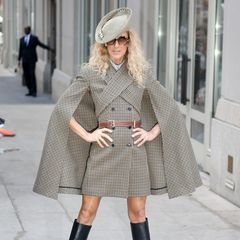 """Woher Céline Dion ihre Outfit-Inspiration nimmt? Wir wissen es nicht. Doch bei diesem """"Michael Kors""""-Cape-Look im Karo-Design und integriertem Blazer-Kleid liegt die Vermutung nahe, dass sich die Sängerin eine berühmteMärchenfigur zum Vorbild genommen hat: Robin Hood. Der schiefeFilzhut und diekniehohen Stiefel machen den Look noch authentischer."""
