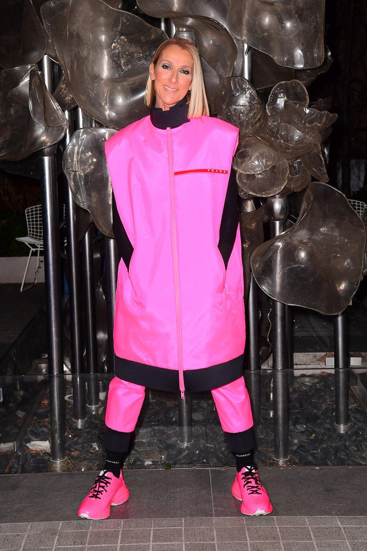 Nach einem Konzert wirft sich Céline Dion erst einmal etwas gemütliches über: In einem pinkfarbenen Oversize-Zweiteiler des Labels Prada posiert die Sängerin entspannt mit den Händen in der Tasche für die Fotografen.