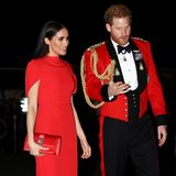 Die Herzogin von Sussex trägt eine bodenlange rote Robe im Stil eines Cape-Kleids von Safiyaa. Auch bei ihren Accessoires setzt Meghan auf Rot: So kombiniert sie Wildleder-Pumps von Aquazzura und eine Satin-Clutch von Manolo Blahnik zu ihrem Dress, die farblich allesamt perfekt aufeinander abgestimmt sind.