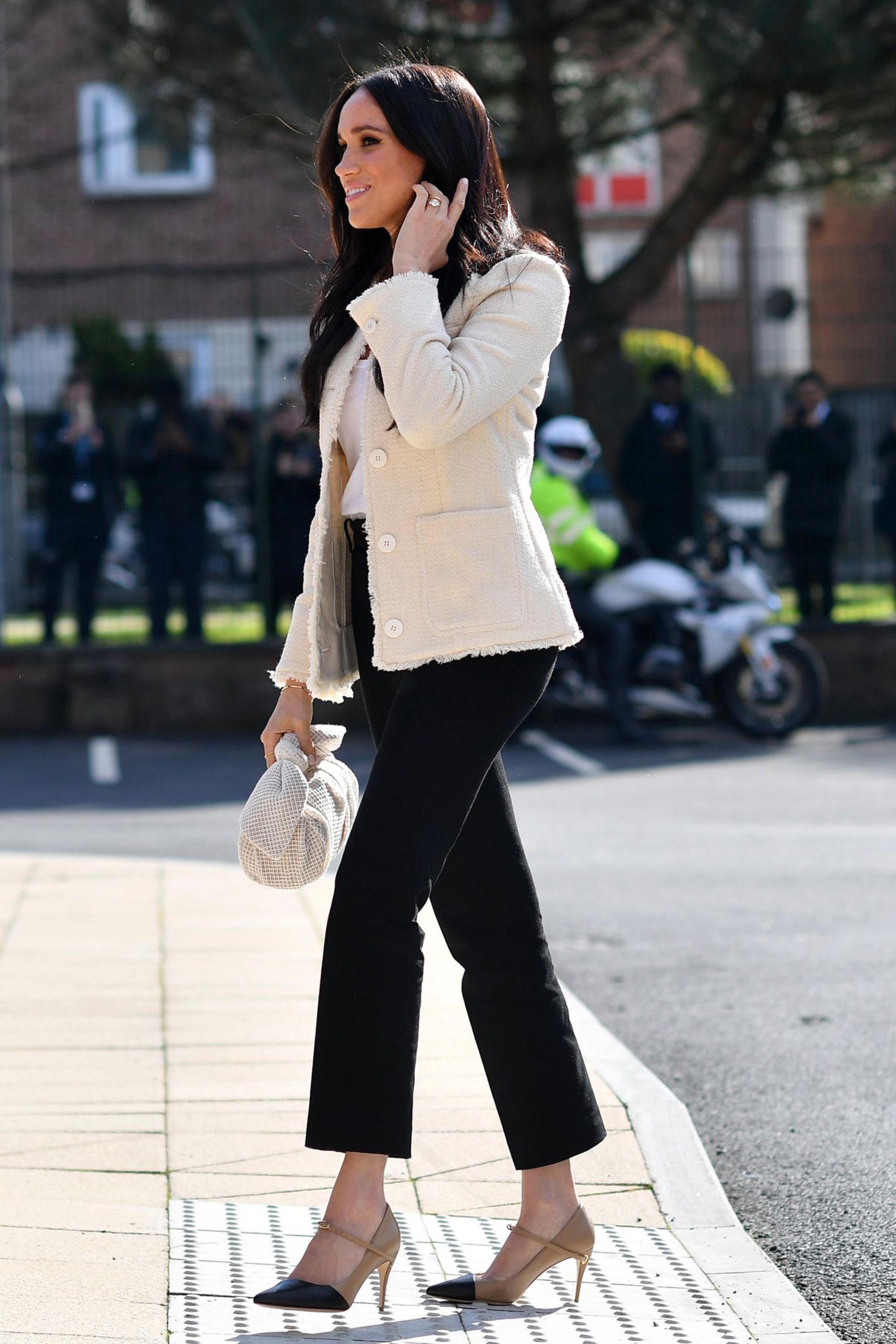 """Für ihren Besuch in Dagenham wählt Herzogin Meghan einen cremefarbenen Bouclé-Blazer des Labels """"ME+EM"""". Darunter trägt sie ein schlichtes, weißes Shirt und kombiniert die hellen Kleidungsstücke zu einer schwarzen Highwaist-Hose von Alexander McQueen. Beide Farbtöne werden außerdem perfekt von ihrenLederpumps aufgegriffen – ein Modell von Jennifer Chamandi für rund 660 Euro. Ein besonderes Accessoire mit einer süßen Schleife trägt die Herzogin in ihrer Hand: die """"Nane""""-Tasche der Londoner Designerin Rejina Pyo."""