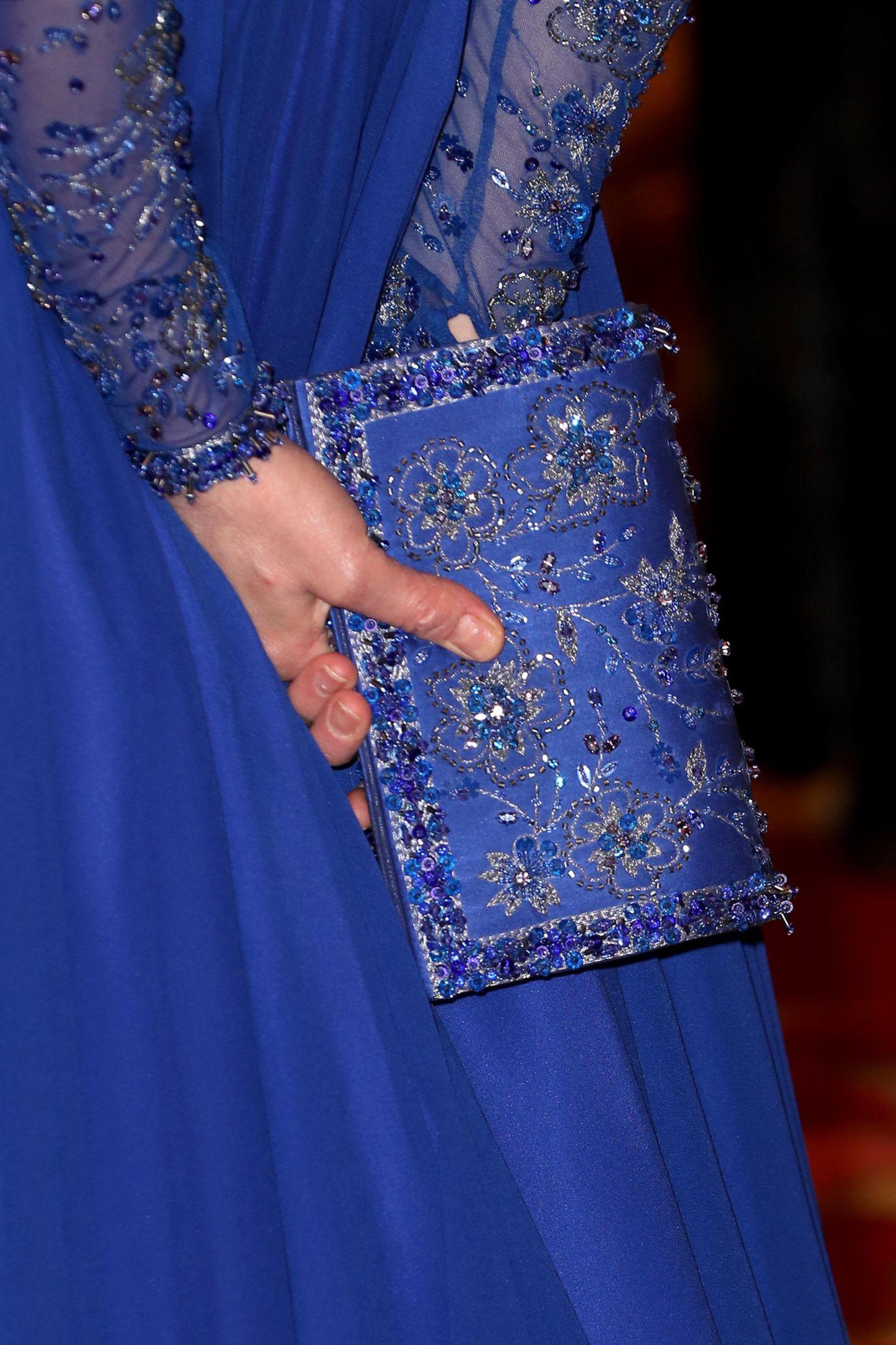 In der Hand hält sie eine blaue funkelnde Clutch, die perfekt zu ihrer Abendrobe passt. Was für ein Look!