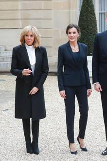 Ob die sich wohl abgesprochen haben? Königin Letizia begleitet ihren Gatten König Felipe beim Staatsbesuch in Frankreich und trifft dabei auch Première Dame Brigitte Macron. Beide Damen setzen auf schlichte Looks: Brigitte trägt beim ersten gemeinsamen Termin einen schlichten Mantel, eine weiße Bluse und Stiefel von Louis Vuitton (ca. 1000 Euro). Letizia setzt auf einen dunkelblauen Anzug, Pumps und eine klassische Perlenkette.