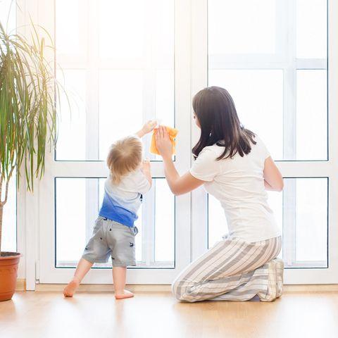 Fenster putzen, Frau mit Kleinkind, großes Fenster im Zimmer