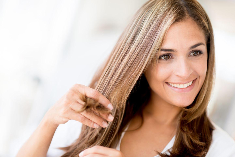 Frau fasst sich in die Spitzen ihrer Haare