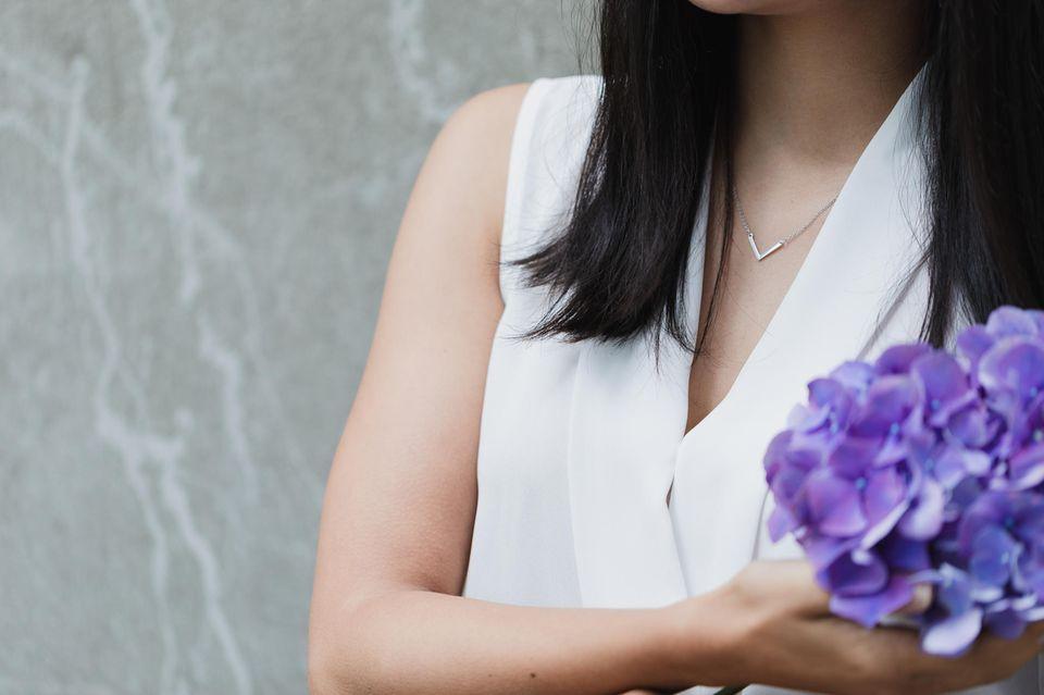 Ausschnitt des Oberkörpers einer Frau mit braunen Haaren, die eine Halskette trägt