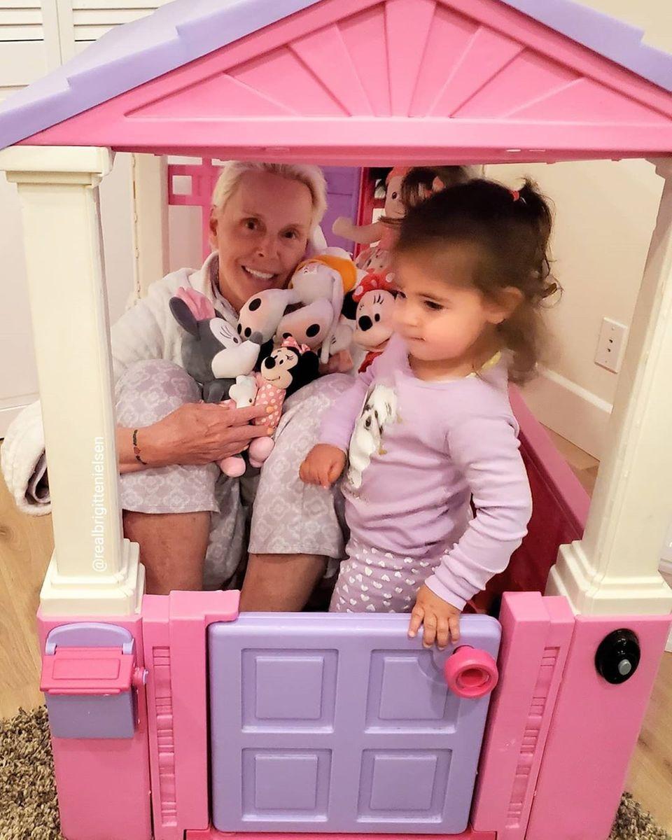 """Auch Brigitte Nielsen nimmt die Aufforderung, zu Hause zu bleiben, sehr ernst. Mit ihrer Tochter Frida und den Kuscheltieren spielt sie """"Zu Hause bleiben"""" in Fridas kleinem pinkfarbenen Eigenheim."""