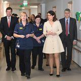 In einem kurzen, beigefarbenen Kleid mit auffälliger Knopfleiste zeigt Eugeniebei einem Krankenhausbesuch ganz schön viel Bein.