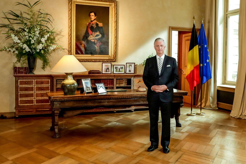 König Philippe von Belgien posiert vorseiner XXL-Kommode im königlichen Palast in Brüssel. XXL-Blumengestecke und betagte Ölgemälde deuten unverkennbar auf das Büro eines Oberhauptes hin.