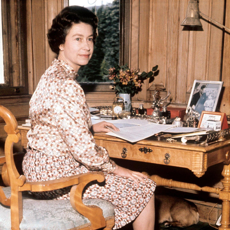 In ihrem königlichen Ferienhaus in Balmoral, Schottland, arbeitet Königin Elizabeth II. in einem mit Holz verkleideten Büro das den Blick auf die grüne Landschaft freigibt. Familienfotos und ein frischer Blumenstrauß zieren das karge Interieur.