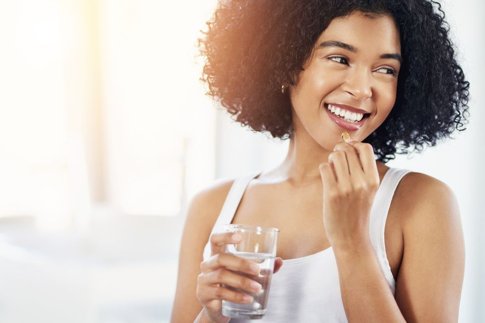 Lächelnde setzt eine Kapsel an den Mund und hält in der anderen Hand ein Glas Wasser