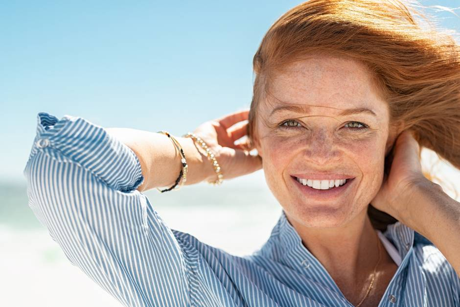 Rothaarige Frau vor hellem Hintergrund lächelt