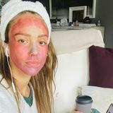 """Jessica Alba arbeitet aus dem Homeoffice heraus und nutzt die Zeit, um sich eine Maske aus ihrer """"Honest"""" Beauty-Serie zu gönnen. Solange bei der Konferenzschaltung die Videoübertragung ausgeschaltet ist - kein Problem."""