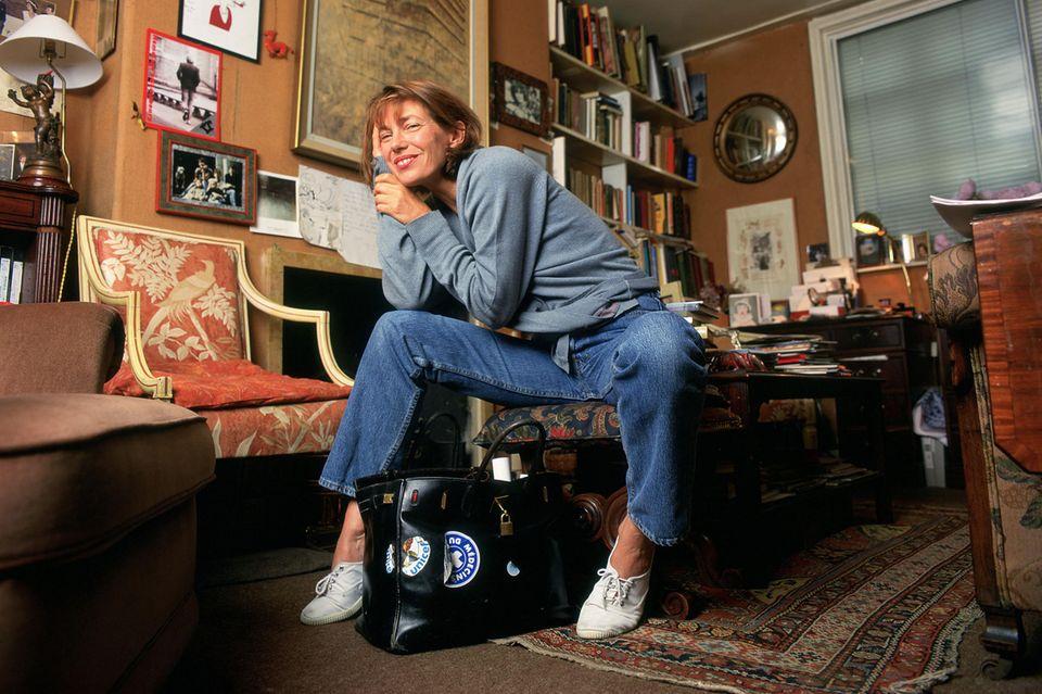 """Sie entwarf die vielleicht begehrteste Tasche der Welt mit: Jane Birkin mit einem beklebten Modell ihrer """"Birkin Bag"""" von Hermès"""