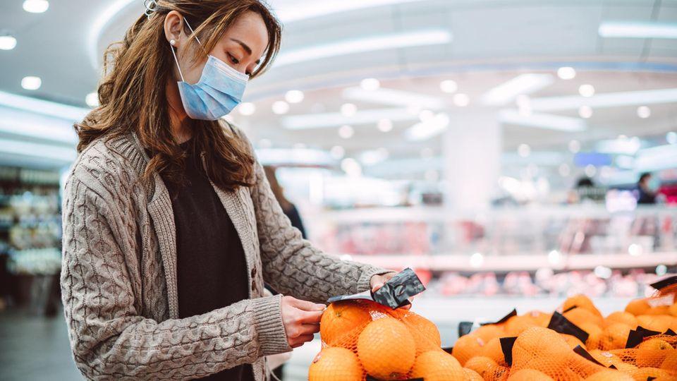 Frau beim Einkaufen mit Mundschutz