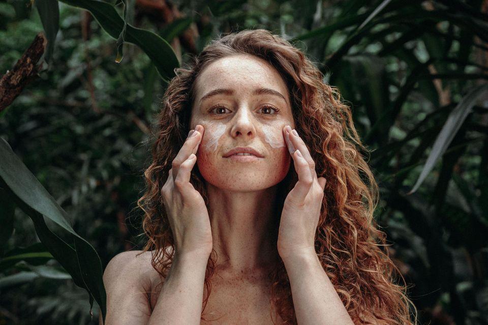 Frau mit roten Locken massiert sich Creme ins Gesicht