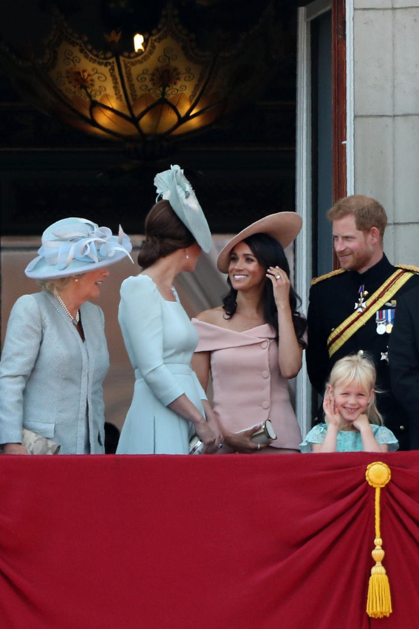 """Meghan wirke nervös, schreibt die englische Presse, zeigt jedoch Verständnis. Dass Kate sich zu ihrer Schwägerin umdreht und mir ihr plaudert, wird als """"süße Geste"""" quittiert. Einziger Kritikpunkt an der Neu-Herzogin: Meghan begehe mit dem Zeigen ihrer nackten Schulter einen Protokollbruch;eine solche Offenherzigkeit gehöre sich nicht für einen Royal."""