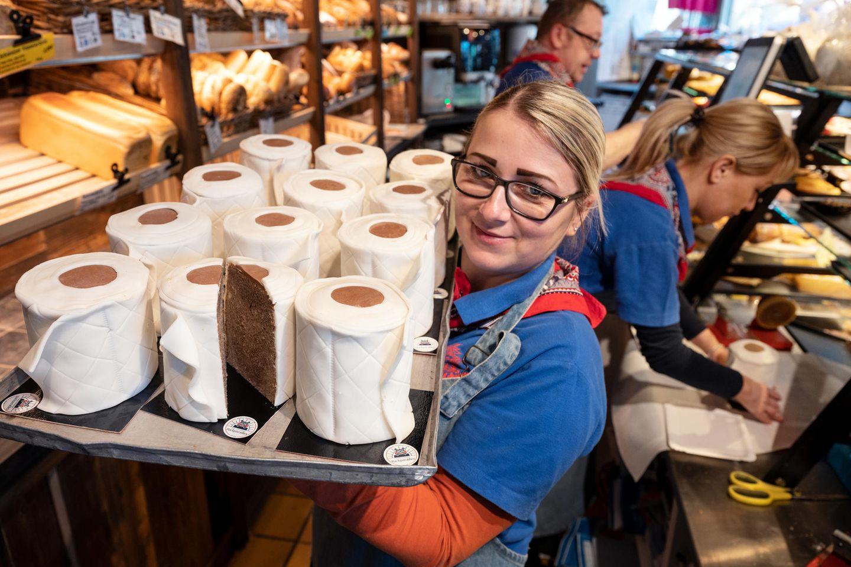 """Eine Verkäuferin der Bäckerei """"Schürener Backparadies"""" aus Dortmund zeigt im Verkaufsraum ein Blech mit runden Marmorkuchen, die mit Fondant umwickelt wie Toilettenpapier-Rollen aussehen. Der Klopapier-Kuchen von Bäcker Kortüm ist in der Corona-Krise zu einem """"Bestseller""""geworden."""