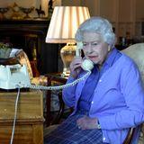 Queen Elizabeth arbeitet während der Coronavirus-Krise im Home Office auf Schloss Windsor. Hier sieht man sie bei einem ihrer wichtigsten Termine: demwöchentlich stattfindendenGespräch mit Premierminister Boris Johnson (in der Regel treffen sich die beiden dazu persönlich im Palast). Absoluter Hingucker auf dem Foto und das Gesprächsthema in den sozialen Netzwerken:das in die Jahre gekommene, aber sehr charmante Telefon der Queen. Doch das ist nicht alles, was es zu sehen gibt. Die Queen hat allerlei Figürchen auf ihrem Schreibtisch platziert:Hunde (genauer gesagt Corgis, ihre Lieblingshunderasse), einen Soldaten und sogar einen kleinen Beef Eater.