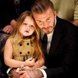 Harper wird schon früh zur kleinen Jetsetterin, die mitihrer Familie um die Welt reist. 2015 begleitet sie Papa David im passenden Mini-Outfit.zur Burberry-Show in Los Angeles.