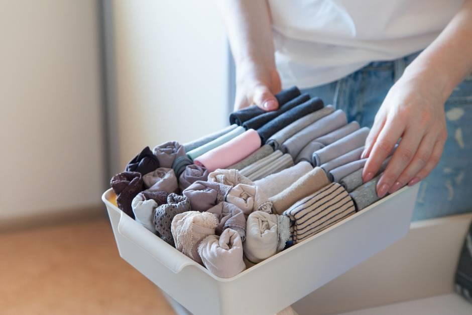 Ausmisten: Frau räumt eine Schublade ordentlich ein