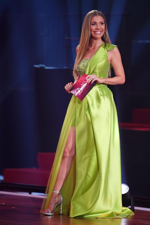 """In einem froschgrünen, bodenlangen Kleid imOne-Shoulder-Schnitt ist die Moderatorin Hingucker der 5. Live-Show von """"Let's Dance"""". Ein tiefer Beinschlitz gibt dem Kleid das gewisse Extra. Apropos Bein: Ein Körperteil, welches Victoria sehr gerne betont. Sehen Sie selbst ..."""