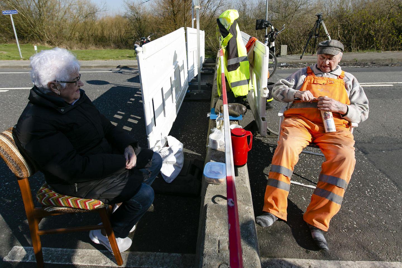Karsten Tüchsen Hansen (r.) und die Dänin Inga Rasmussen sitzen am deutsch-dänischen Grenzübergang. Wegen des Coronavirus ist dem Paar derzeit nicht erlaubt, sich zu besuchen.