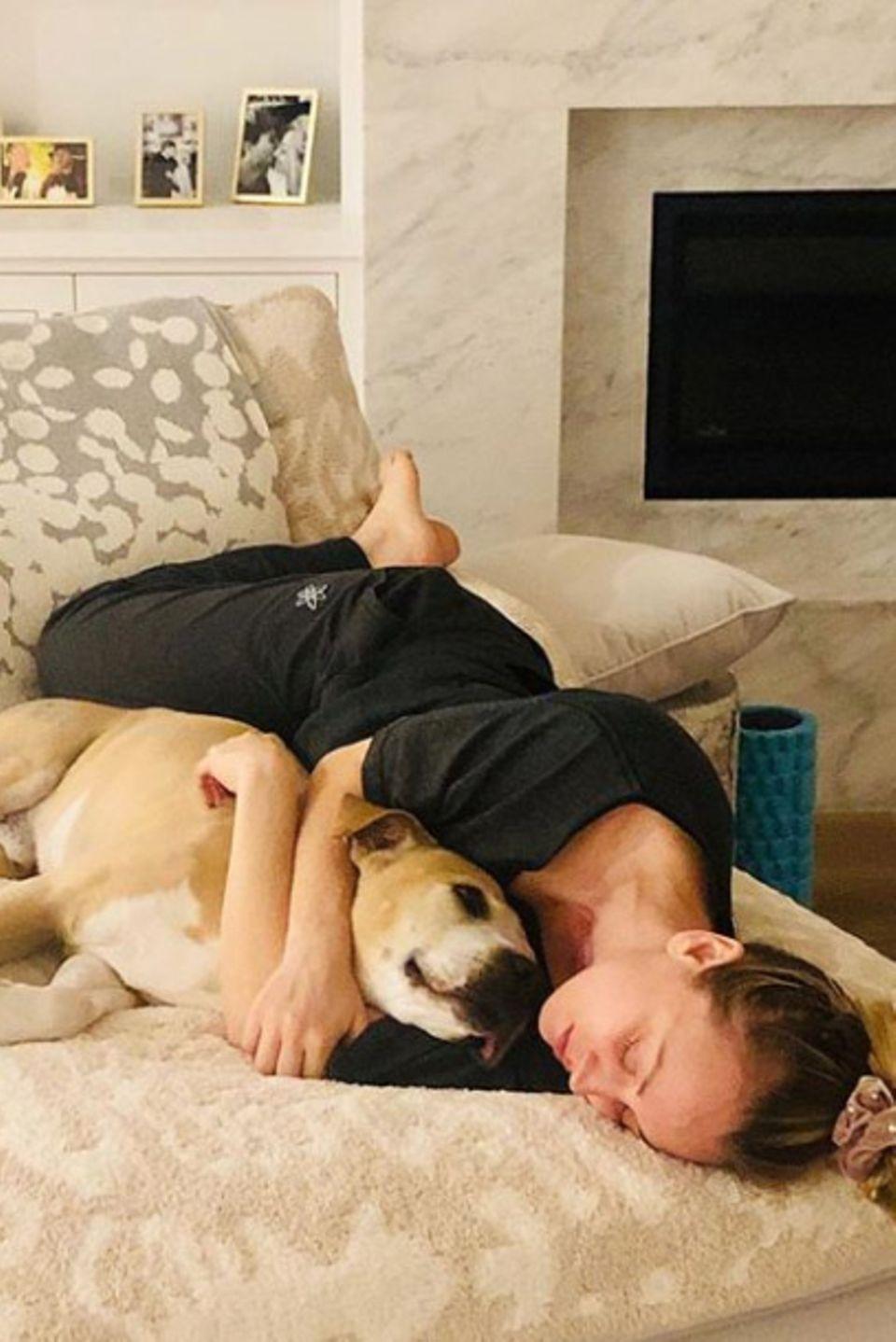 """Eingekuschelt mit Hund Norman lässt sich auch für """"Big Bang Theory""""-Star Kaley Cuocodie häusliche Quarantäne gut aushalten."""