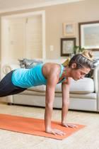 junge Frau plankt auf Yogamatte im Wohnzimmer
