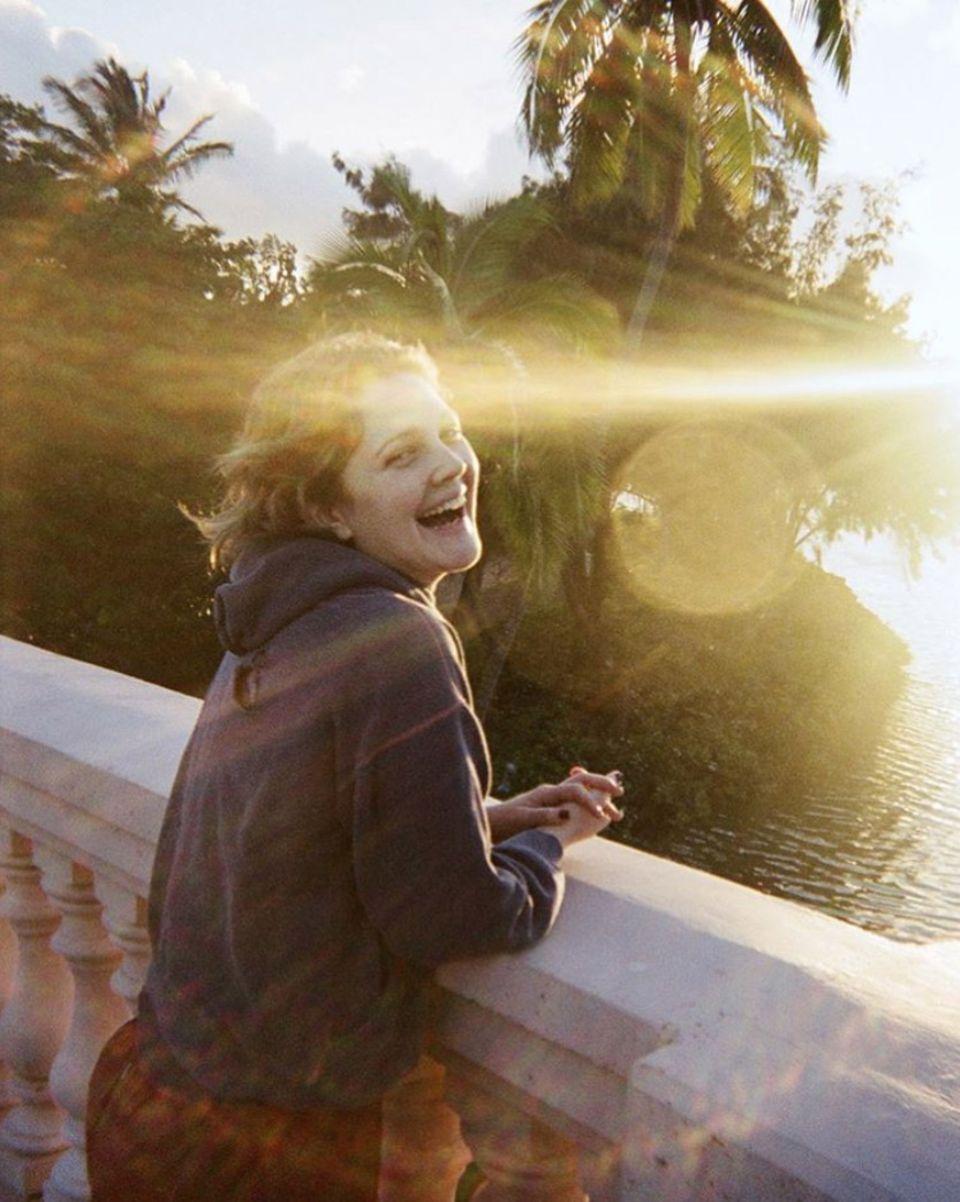 """1. April 2020  Das wünschen wir uns jetzt sehr: Sommer, Sonne, Urlaub. Drew Barrymorenimmt uns zumindest in Gedanken mit auf eine kleine (Zeit-)Reise. In einem Artikel für das """"Condé Nast Traveler""""-Magazin berichtet sie von ihrer ersten Reise nach Hawaii und teilt dazu diesen fröhlichen Schnappschuss von 1993, auf dem die Schauspielerin gerade mal süße 18 Jahre jung ist."""