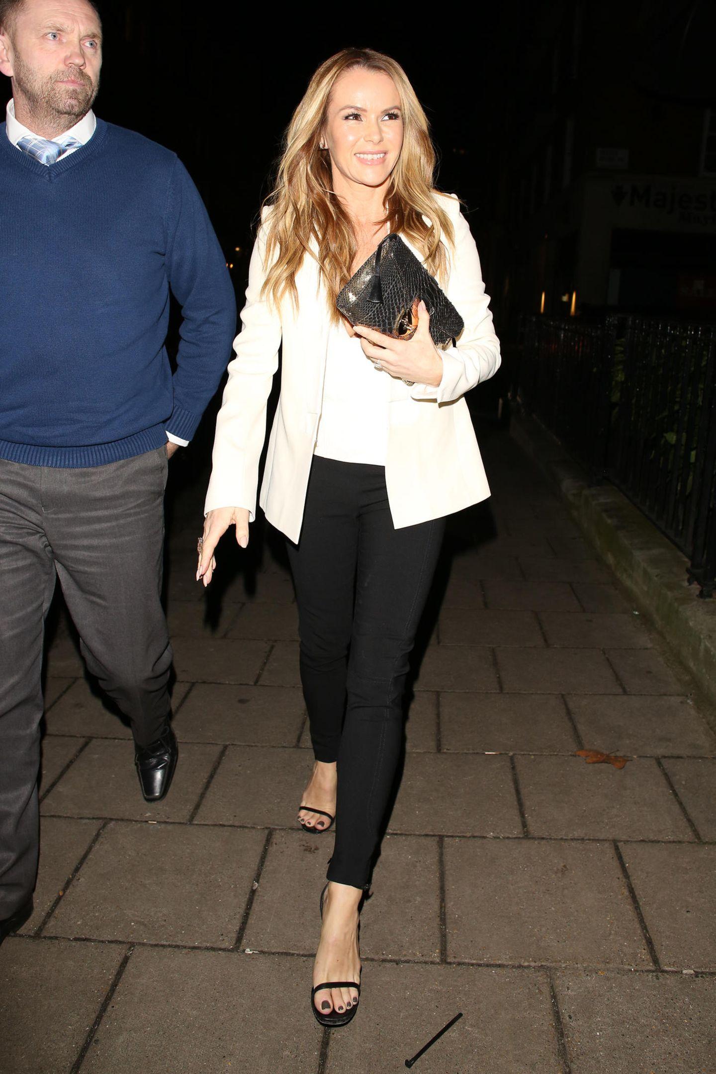Das liegt daran, dass auch Amanda Holdendie Kombination aus cremefarbigen Blazer, weißem T-Shirt und schwarzer Stoffhose liebt. Im Januar 2018 trug sie diesen Look zu einer Party in London.