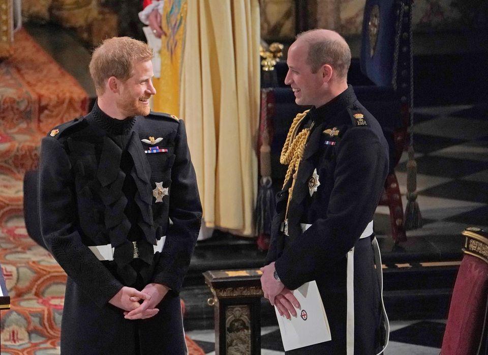 """19. Mai 2019  Der Tag der Hochzeit ist gekommen. Harry wartet in der St George's Chapel auf Schloss Windsor nervös auf das Erscheinen seiner großen Liebe Meghan. An seiner Seite: Trauzeuge William, der es schafft, seinem kleinen Bruderein Lächeln aufs Gesicht zu zaubern. Ob die beiden sich an den 29. April 2011 zurückerinnern? Damals war es Harry gewesen, der seinem Bruder vor dem Altar beigestanden hatte. Unvergessen die Worte, die Harry ihm beim Eintritt von Kate Middleton zuraunte: """"Also ... sie sieht wunderschön aus, das kann ich dir sagen."""""""