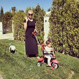 """Brigitte Nielsen ist mit ihren beiden """"Kleinen"""", wie sie sie auf Instagram nennt, voll beschäftigt. An einem wunderbaren sonnigen Tag schiebt sie Tochter Frida auf dem Dreirad durch den Garten. Und der Familienhund hat auch gleich Auslauf."""