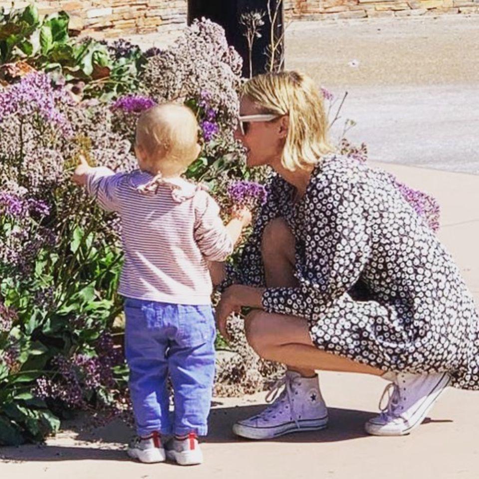 """Diane Kruger zeigt ihre Tochter nicht oft, deshalb freuen wir uns über dieses fast sommerliche Foto. Auf Instagram teilt sie mit, dass ihr trotz der Einschränkungen in der Coronaviruskrise eines sehr wichtig ist: """" Ich muss ihr zeigen, stehen zu bleiben und an den Rosen zu riechen (offensichtlich sind es keine Rosen, aber egal, was es ist...)""""."""